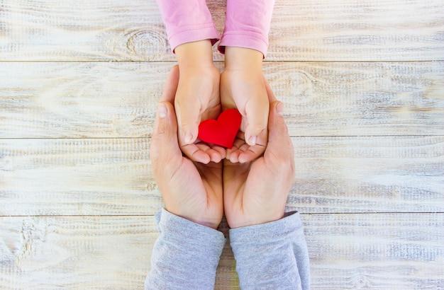 Bambino e padre hanno un cuore nelle loro mani. messa a fuoco selettiva