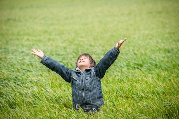 Bambino eccitato sul bellissimo campo di erba verde giallo