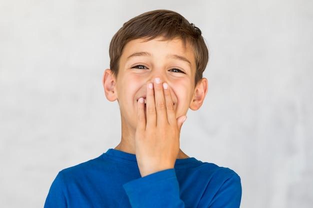 Bambino felice che copre la bocca