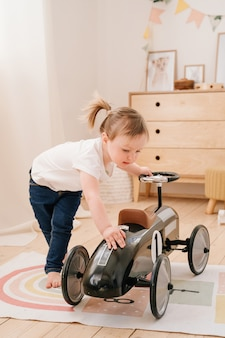Bambino felice che gioca a casa. una ragazza con le code di cavallo gioca nella stanza e cavalca un'auto giocattolo retrò.