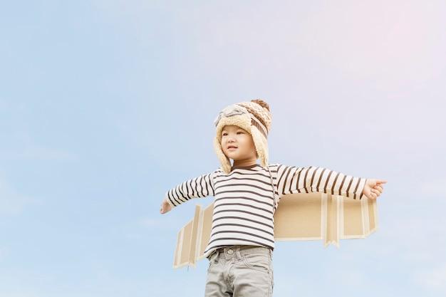 Bambino felice che gioca con le ali del giocattolo contro il fondo del cielo di estate