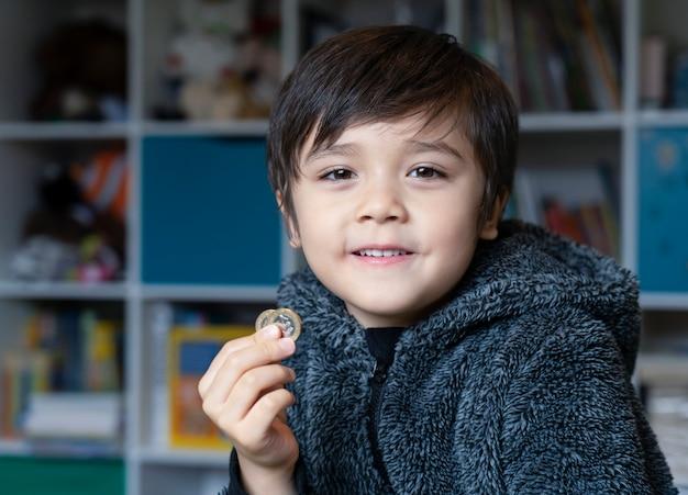 Bambino felice che indossa pigiami pieni di pieni che tengono due monete da una libbra