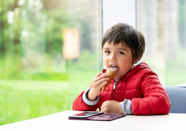 Bambino felice che lecca un gelato, ragazzo prescolare di rilassamento che si siede al tavolo in un caffè