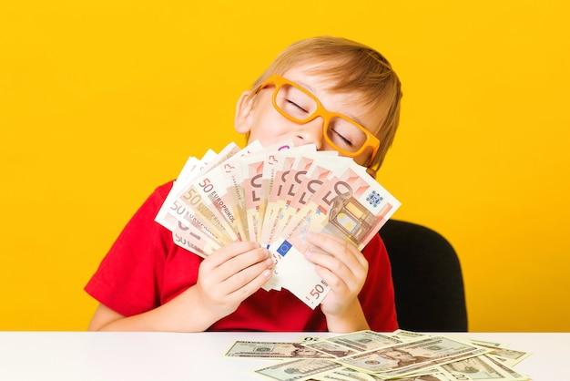 Bambino felice che mostra fan di soldi. soldi per l'educazione futura. ragazzo carino conta i suoi soldi. alfabetizzazione finanziaria dei bambini.