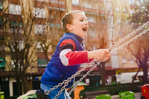 Bambino felice che oscilla in un parco della città con il grande sorriso