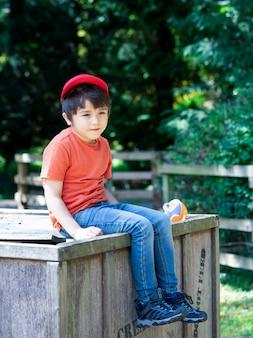 Bambino felice che porta il cappello dello spiritello malevolo che si siede scatola di legno nel parco, concetto positivo dei bambini