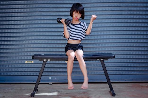 Bambino felice che si siede sulla panchina per l'esercizio su manubri