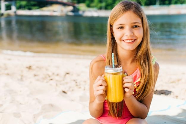 Bambino felice che sorride con la bevanda sulla spiaggia