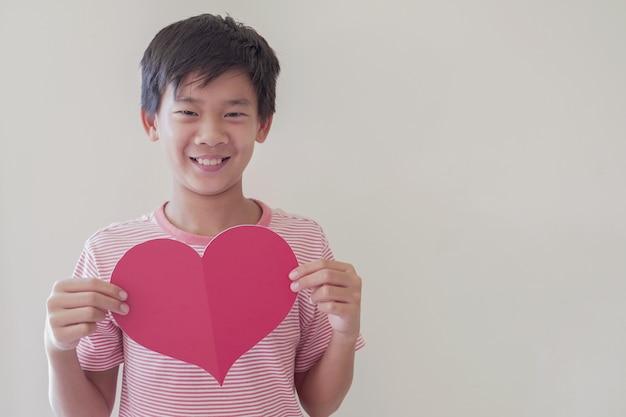 Bambino felice che tiene grande cuore rosso