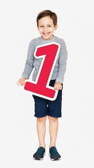 Bambino felice che tiene il numero uno