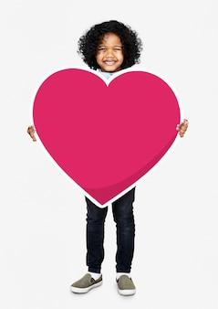 Bambino felice che tiene un'icona del cuore