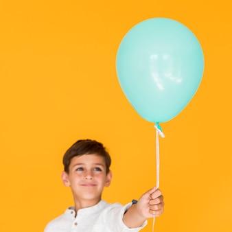 Bambino felice che tiene un pallone blu