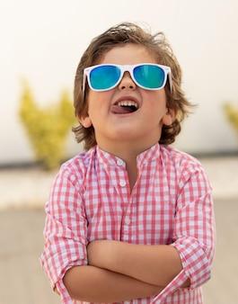 Bambino felice con gli occhiali da sole in giardino