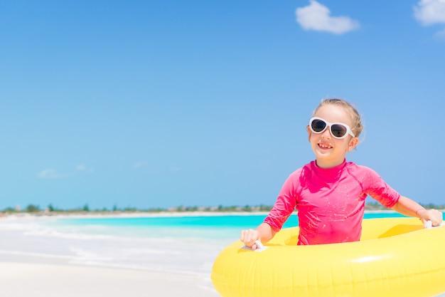 Bambino felice con il cerchio di gomma gonfiabile divertendosi sulla spiaggia