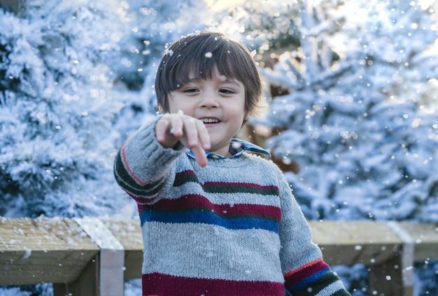 Bambino felice con la faccia sorridente che gioca con le bolle di schiuma con bokeh sfocato