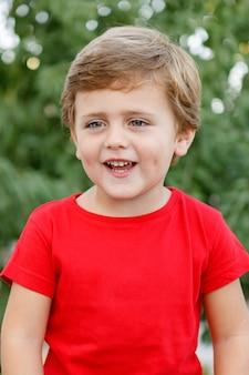 Bambino felice con la maglietta rossa nel giardino