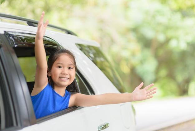 Bambino felice con le braccia alzate dalla macchina di finestra
