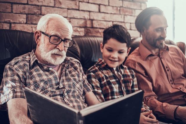Bambino felice con padre e nonno in barbiere