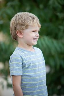 Bambino felice con t-shirt blu in giardino