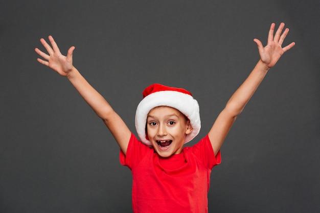 Bambino felice del ragazzino che porta il cappello di santa di natale