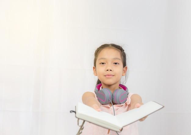 Bambino felice della bambina che sta con le cuffie e il libro della tenuta della mano