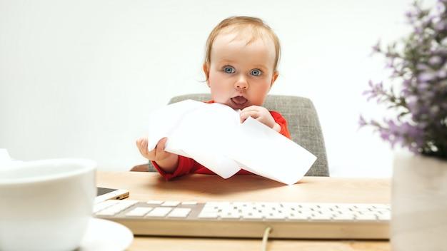 Bambino felice della neonata del bambino che si siede con la tastiera del computer isolata su un fondo bianco