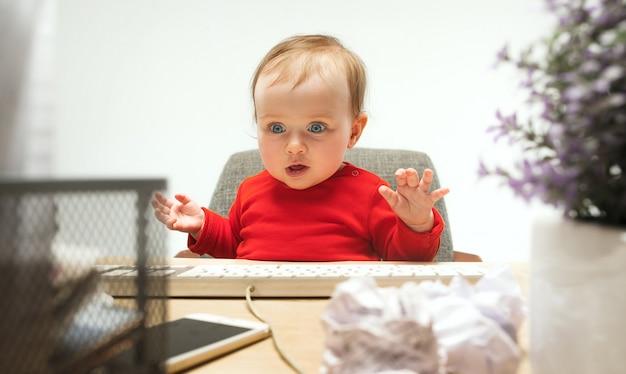 Bambino felice della neonata del bambino che si siede con la tastiera del computer isolata