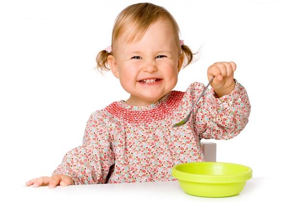 Bambino felice di mangiare, isolato su sfondo bianco