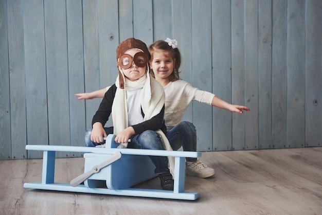 Bambino felice in cappello pilota che gioca con l'aeroplano di legno contro. infanzia. fantasia, immaginazione. vacanza