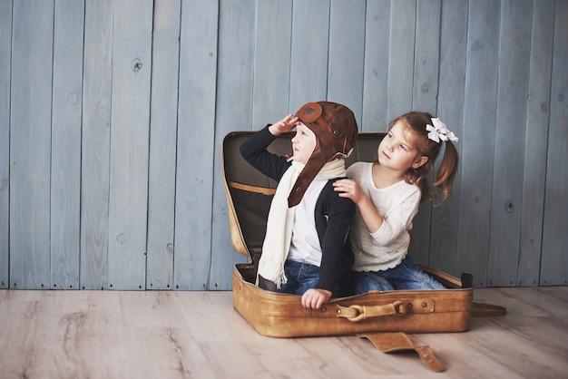 Bambino felice in cappello pilota e bambina che giocano con la vecchia valigia. infanzia. fantasia, immaginazione. viaggio