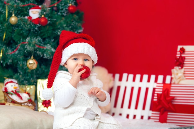 Bambino felice in interni di natale, cappello di babbo natale con regali