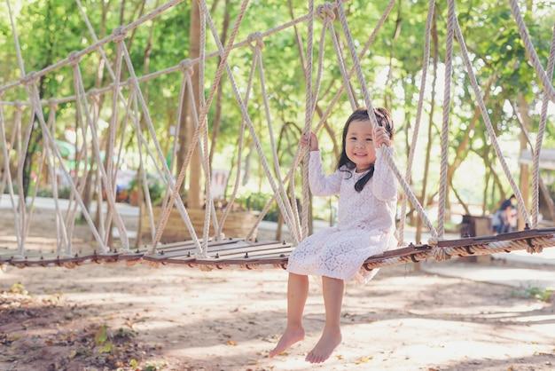 Bambino felice in natura, bambina in abito bianco