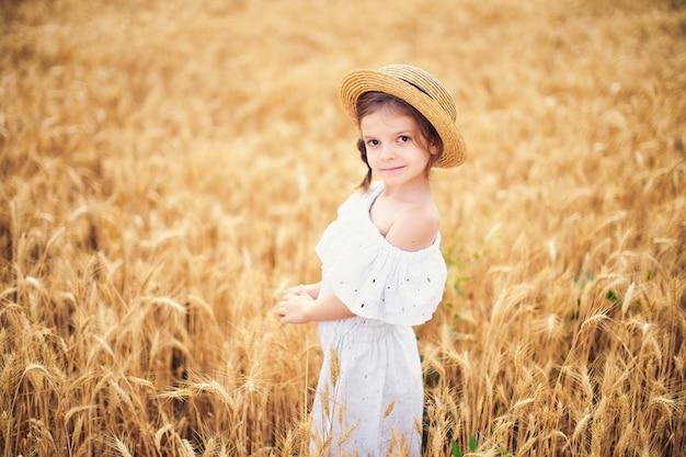 Bambino felice nel campo di grano in autunno. bella ragazza in abito bianco e cappello di paglia si divertono con il gioco, la raccolta