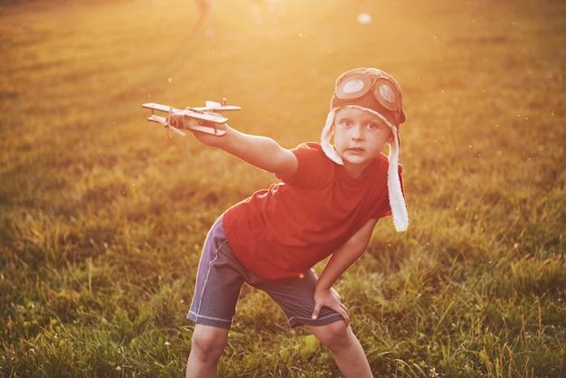 Bambino felice nel casco pilota giocando con un aeroplanino giocattolo di legno e sognando di diventare volante