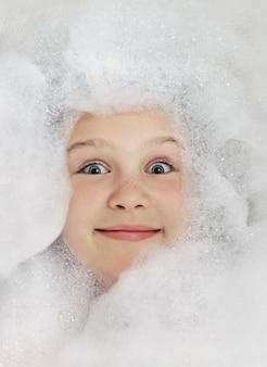 Bambino felice nella vasca da bagno, nuoto nella schiuma