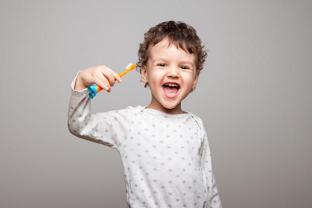 Bambino felice, ragazzo, con uno spazzolino da denti in mano, ride e gioisce. sorriso spalancato, denti da latte bianchi. igiene orale ogni giorno. isolato.