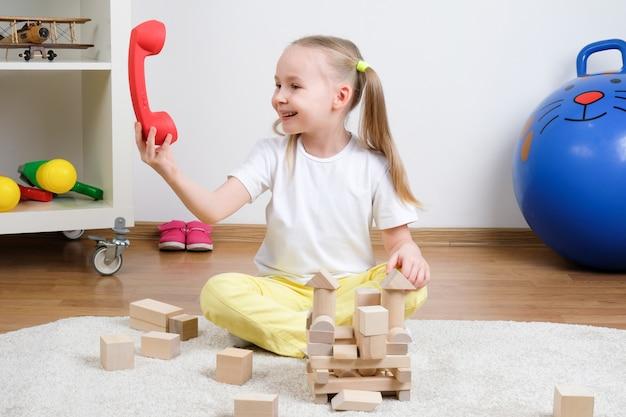 Bambino gioca con cubi di legno e un telefono sul pavimento