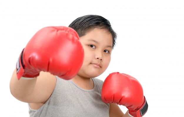 Bambino grasso che combatte con i guantoni da pugile rossi isolati