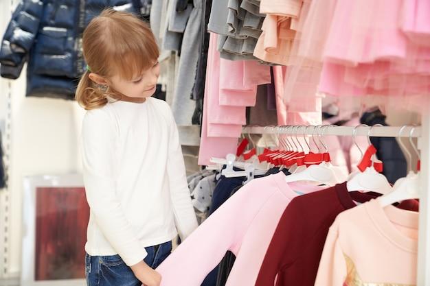 Bambino grazioso che sceglie abbigliamento in deposito.