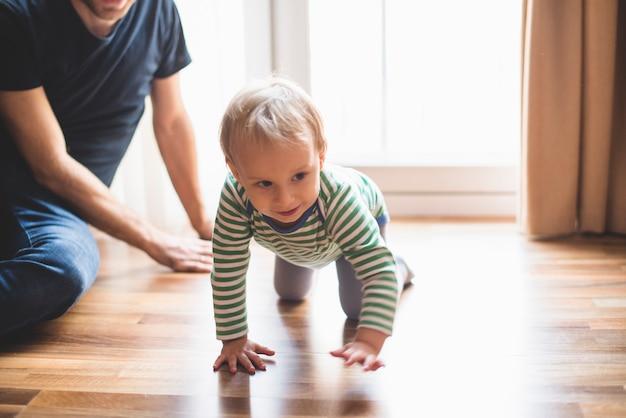 Bambino imparare a strisciare con il padre in background