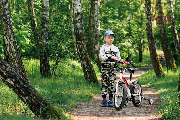 Bambino in bicicletta nella foresta al mattino presto. ragazzo che cicla all'aperto nel casco