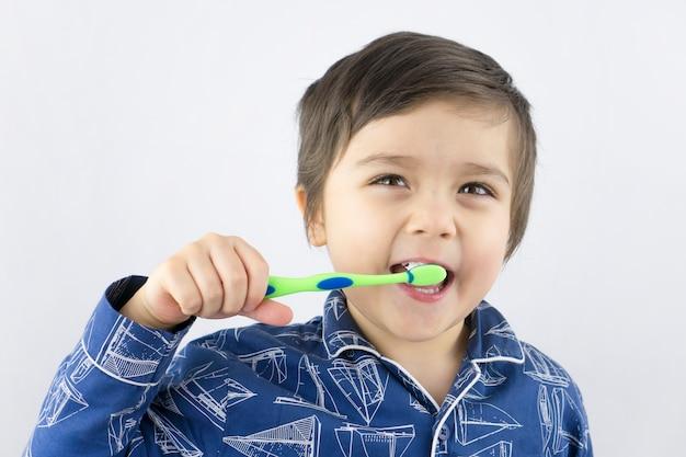 Bambino in buona salute che pulisce i suoi denti con la faccia sorridente
