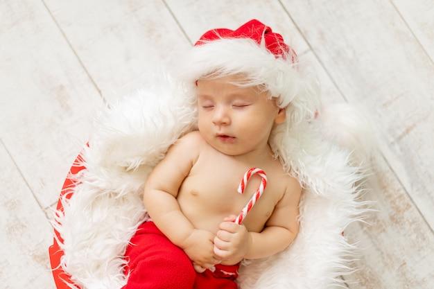 Bambino in costume da babbo natale che dorme su uno sfondo di legno chiaro
