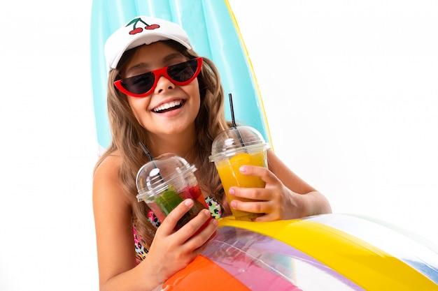 Bambino in costume da bagno e occhiali da sole in vacanza estiva, un largo sorriso sul suo volto