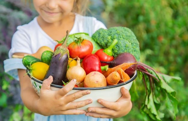 Bambino in giardino con verdure nelle sue mani.