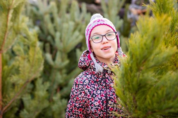 Bambino in giovane età che sceglie e che decora un albero di natale