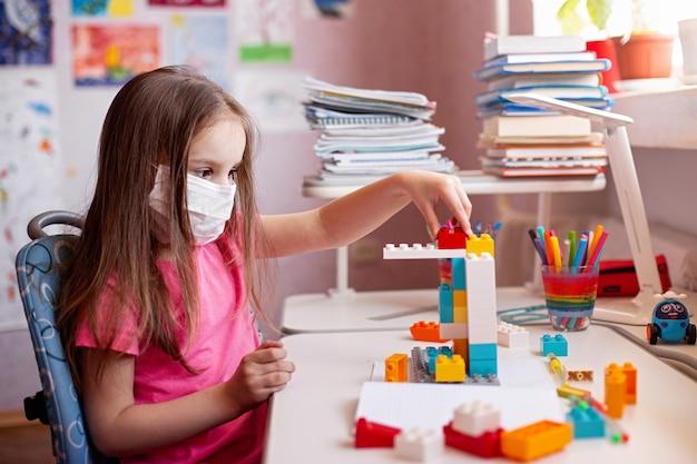 Bambino in maschera facendo i compiti e gioca con il suo giocattolo preferito a casa