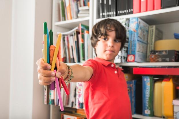 Bambino in piedi con le matite colorate