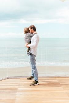 Bambino in piedi della holding dell'uomo sulla spiaggia