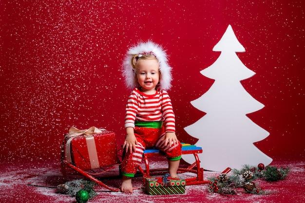 Bambino in pigiama di natale e cappello santa cattura neve seduto su una slitta con confezione regalo e grande albero di natale bianco su sfondo rosso